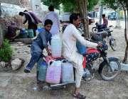 حیدر آباد: موٹر سائیکل سوار پینے کے لیے صاف پانی بھر کر لیجا رہا ہے۔