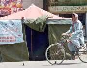 لاہور: ایک سائیکل سوار ایمرجنسی ریلیف کیمپ برائے مون سون کے سامنے سے ..