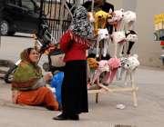 راولپنڈی: صدر بازار میں ایک خاتون بچوں کی ٹوپیاں سجائے فروخت کے لیے ..