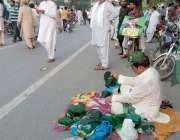 لاہور: مال روڈ پر چیئرنگ کراس میں ایک شخص (ن) لیگ کے پرچم والی ٹوپیاں ..