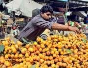 ملتان: ریڑھی بان فروخت کے لیے موسمی پھل سجا رہا ہے۔