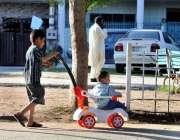 اسلام آباد: ایک بچہ چھوٹے بچے کو سٹالر میں بٹھائے لیجا رہا ہے۔