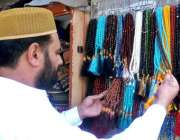 لاہور: ایک شہری مال روڈ پر مسجد شہداء کے باہر دکان سے تسبیح خرید رہا ..