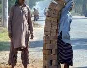 ملتان: مزدور تعمیراتی کام کے لیے اینٹیں اٹھا رہا ہے۔