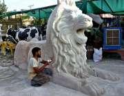 لاہور: محنت کش شیر کا ماڈل تیار کر رہا ہے۔