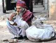 ملتان: ایک معمر محنت کش کار آمد اشیاء اکٹھی کرنے کے بعد ناشتہ کر رہا ..