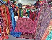 لاہور: دکاندار گاہکوں کو متوجہ کرنے کے کپڑے سجا رہا ہے۔