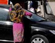 راولپنڈی: صدر کے علاقہ میں ایک خانہ بدوش خاتون گاڑی صاف کرے میں مصروف ..