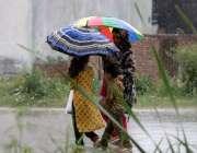 راولپنڈی: خواتین بارش سے بچنے کے لیے چھتری تانے جا رہی ہیں۔