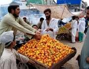 اسلام آباد: شہری سڑک کنارے لگی ریڑھی سے آڑو خرید رہے ہیں۔