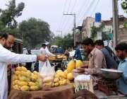 فیصل آباد: شہری سڑک کنارے لگے سٹال سے آم خرید رہے ہیں۔