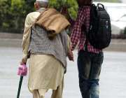 راولپنڈی: ایک نوجوان بارش کے دوران چھتری دے کر معمر شخص کی مدد کر رہا ..