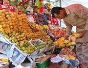 اسلام آباد: دکاندار فروخت کے لیے تازہ پھل سجا رہا ہے۔