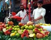 پشاور: ریڑھی بان گاہکوں کو متوجہ کرنے کے لیے تازہ پھلوں کا جوس بنا رہا ..