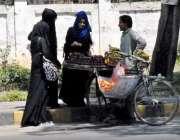 راولپنڈی: خواتین سڑک کنارے فروٹ خرید رہی ہیں۔