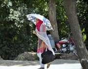 اسلام آباد: خاتون گرمی کی شدت سے بچنے کے لیے چھتری تانے جا رہی ہے۔