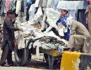راولپنڈی: شہری سڑک کنارے لگے سٹال سے استعمال شدہ کپڑے خرید رہے ہیں۔