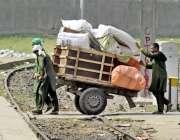 لاہور: ریلوے اسٹین پر قلی ہتھ ریڑھے پر مسافروں کا سامان رکھ کر لیجارہے ..