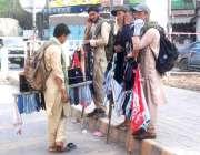 لاہور: محنت کش رومال اور فیس ماسک فروخت کرنے کے لیے سڑک کنارے کھڑے ہیں۔