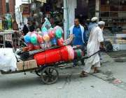 پشاور: معمر محنت کش ہتھ ریڑپھی پر سامان رکھے لیجا رہا ہے۔