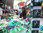 راولپنڈی: جشن یوم آزادی کے موقع پر خواتین ایک سٹال سے جھنڈیاں خرید رہی ..