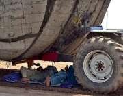 سرگودھا: ٹریکٹر ٹرالی کا ڈرائیور اور ہیلپر ٹرالے کے سائے میں آرام کر ..