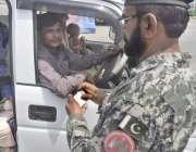 لاہور: سیکیورٹی اہلکار شہر میں داخل ہونیوالی گاڑی میں سوار لوگوں کی ..