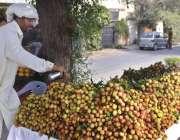 لاہور: ریڑھی بان لیچی کو تازہ رکھنے کے لیے پانی کا چھڑکاؤ کر رہا ہے۔