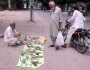 لاہور: ایک شخص سرک کنارے بیٹھا پرانی اشیاء فروخت کر رہا ہے۔