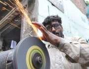 لاہور: عیدالاضحی کی آمد پر ایک دکاندار چھریاں تیز کر رہا ہے۔