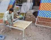 لاہور: ایک محنت کش چارپائی بن رہا ہے۔