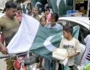 لاہور: اردو بازار میں ایک پولیس اہلکار قومی پرچم خریدنے کے لیے پسند ..