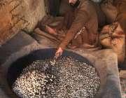 راولپنڈی: دکاندار بھٹی پر مونگ پھلی بھون رہا ہے۔