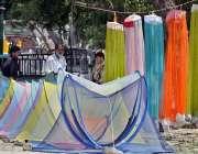راولپنڈی: محنت کش سڑک کنارے مچھردانیاں سجائے گاہکوں کا منتظر ہے۔