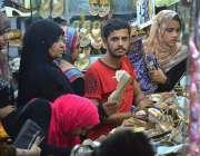 حیدر آباد: عید کی تیاریوں میں مصروف خواتین ایک سٹال سے جوتے پسند کر ..