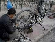 لاہور: نیلا گنبد روڈ پر ایک مکینک سائیکل کی مرمت کر رہا ہے۔