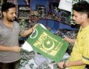 لاہور: ایک نوجوان14اگست کو جشن آزادی کے لیے ٹی شرٹ پسند کر رہا ہے۔