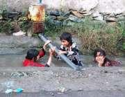 پشاور: گرمی کی شدت کم کرنے کے لیے بچے نالے میں نہا رہے ہیں۔