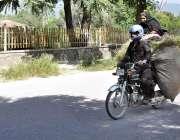 اسلام آباد: خاتون موٹر سائیکل پر رکھے گئے گھاس کے اوپر خطرناک انداز ..