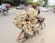 لاہور: ایک شخص گھر کا چولہا جلانے کے لیے لکڑی سائیکل پر رکھے جا رہا ہے۔