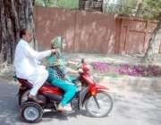 لاہور: ایک خاتون موٹر سائیکل پر جا رہی ہے۔