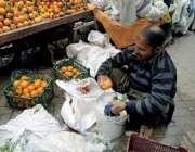 رائے ونڈ: ایک پھل فروش مالٹے صاف کرنے میں مصروف ہے۔