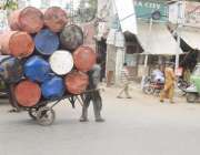 لاہور: ایک محنت کش ہتھ ریڑھی پر لوہے بھاری ڈرم رکھے جا رہے ہیں۔