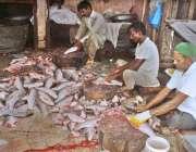 لاہور: دکاندار فروخت کے لیے مچھلی کی صفائی ستھرائی کر رہے ہیں۔