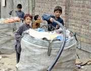 لاہور: بچے کباڑ خانے میں چھانٹی کئے گئے مال کو بورے میں ڈال رہے ہیں۔