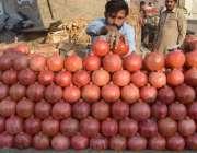 لاہور: ایک شخص انار فروخت کنے کے لیے ریڑھی پر سجارہاہے۔