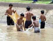 ملتان: خانہ بدوش بچے مقامی نہر سے مچھلیاں پکڑ رہے ہیں۔