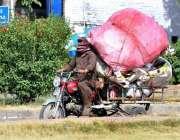 اسلام آباد: ایک شخص چنگچی موٹر سائیکل پر اوورلوڈنگ کیے جارہا ہے جو کسی ..
