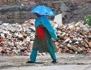 راولپنڈی: خاتون گرمی اور دھوپ کی شدت سے بچنے کے لیے چھتری تانے جار ہی ..