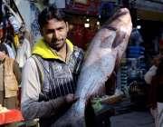 اٹک: ایک دکاندار بڑی سائز کی مچھلی دکھا رہا ہے۔